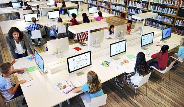 Teacher in computer lab with children